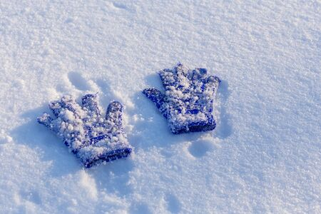 Two kids blue mittens with adhering snow lying down on snow Imagens