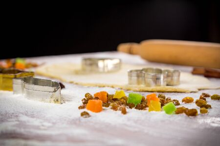 dough on table with dried fruits and cutters