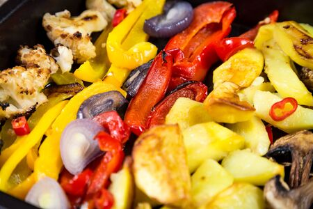 Chopped stewed vegetables on tray, food background, closeup