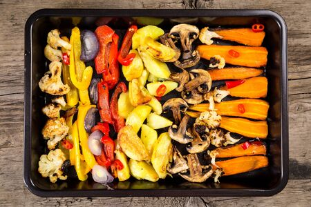 Chopped stewed vegetables on tray at wooden table, food background, flat lay