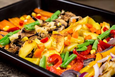 Chopped stewed vegetables on tray at wooden table, food background, closeup
