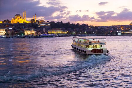 Istanbul. Turkey. Evening view near Galata Bridge to the Golden Horn bay with passenger ship and silhouette of Suleymaniye Mosque
