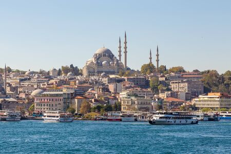 Istanbul. Turkey - 21 october 2014: passenger boats near station Eminonu on the Golden Horn bay and silhouette of Suleymaniye Mosque on the cityscape