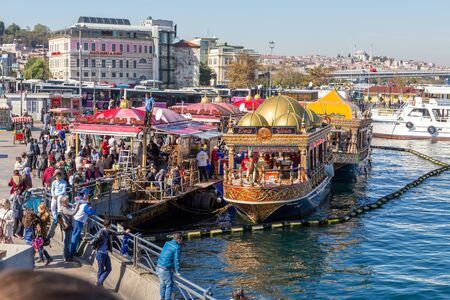 Istanbul. Turkey -21 october 2014: Fishing boats restaurants in Eminonu pier near Galata Bridge at the Golden Horn bay, traditional street food