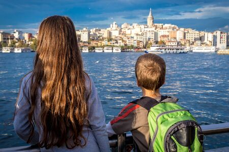 Two kids looking to cityscape of Istanbul with silhouette of Gal
