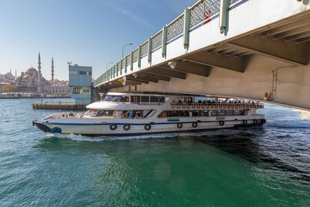 Ferry boat ship passes under the Galata Bridge at Golden Horn bay, Istanbul, Turkey Imagens