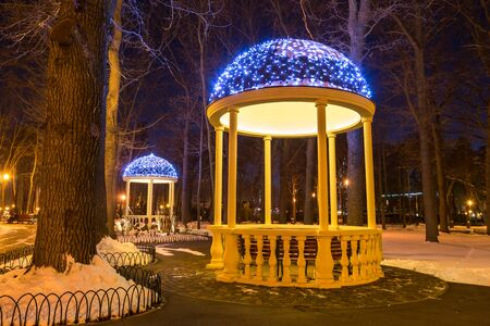 Two arbors with electric garlands in winter city park, evening holiday decorations. Kharkiv, Ukraine Imagens