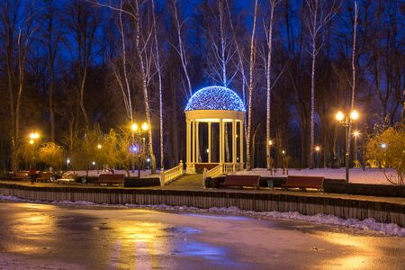 Gazebo with electric garlands in winter city park, evening holiday decorations. Kharkiv, Ukraine
