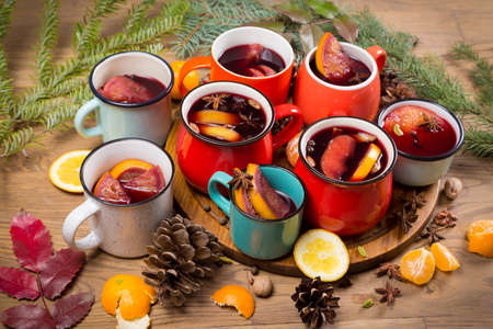Many colorful cups with mulled wine on festive table