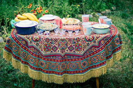 Decorated table covered with an old tablecloth outdoors. photo
