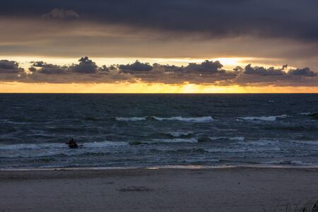 Man in a kayak at Sunset over the Baltic sea with dramatic clouds.