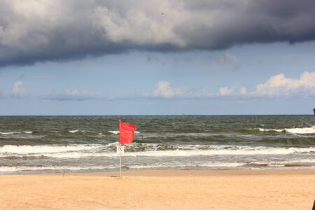 Red flag on the beach of baltic sea. Dangerous. Stock Photo
