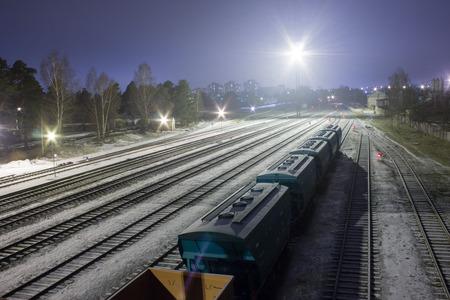 The train arrives on the snowy railway station.