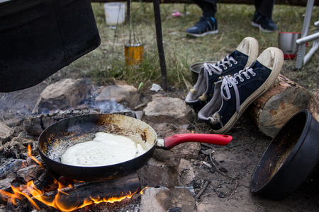 Pancake cooked on a fire in a frying pan with a red pen, shoes on background. Stock Photo