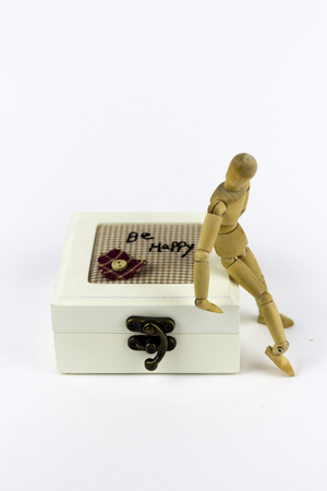 jewlery: Wooden puppet sitting on a jewellery box on a white background