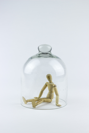 trapped: Wooden puppet trapped in a glass bell cage, on a white background