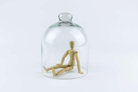 marioneta de madera: Marioneta de madera atrapados en una jaula campana de vidrio, sobre un fondo blanco