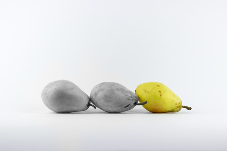 desaturated: Three pears on a white background, one of them desaturated