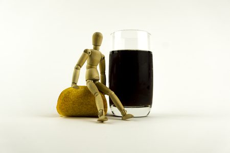 calories poor: Wooden doll sitting on a pile of chips, near a glass of cola