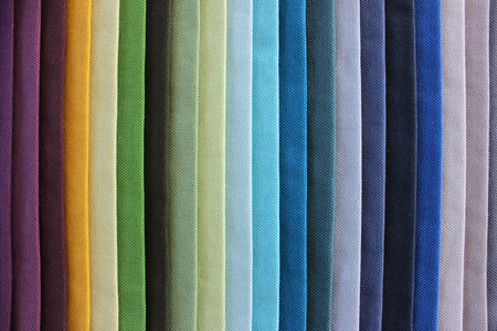 sex discrimination: Different coloured samples of cloth, displayed on a table in a rainbow pattern