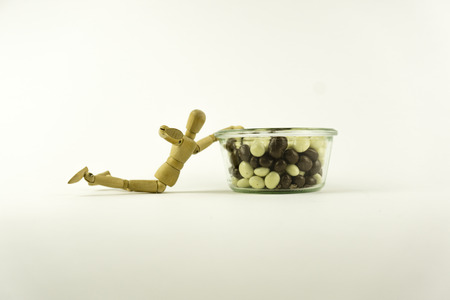 calories poor: Wooden doll trying to eat a candy Stock Photo
