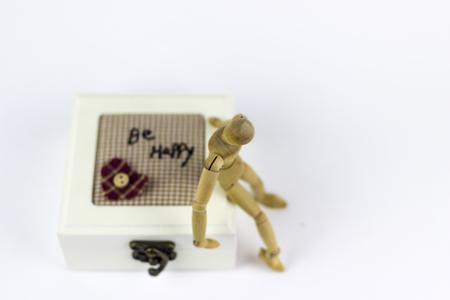 marioneta de madera: Marioneta de madera que se sienta en una caja de joyas sobre un fondo blanco