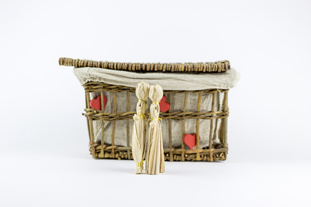 puppet woman: Two straw dolls kissing in front of an old rattan box, on a white background Stock Photo
