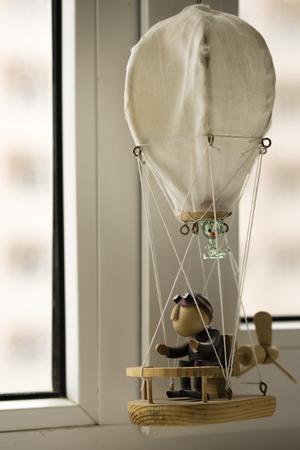marioneta de madera: marioneta de madera, con un gato, en un globo, mirando por la ventana.