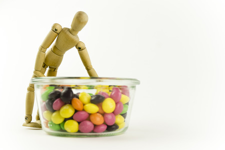 calories poor: Happy wooden doll with a jar of candies