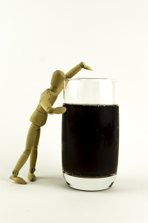 calories poor: Wooden doll trying to have a drink Stock Photo
