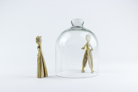 prisoner of love: Man and woman straw dolls, divided by a glass bell, on a white background Stock Photo