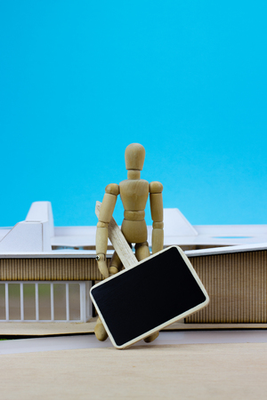 house facades: Wooden man with sign in front of miniature building Stock Photo