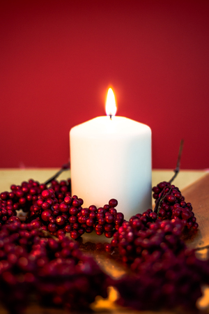 christmas perfume: Lit candle for christmas on red background Stock Photo