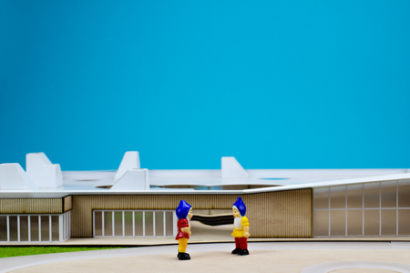arhitecture: Two garden dwarfs in front of a miniature buiding
