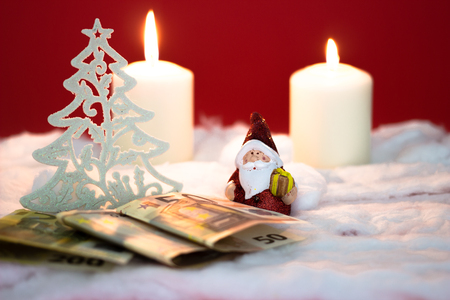 burning money: Santa Claus with burning candles and money on red background Stock Photo