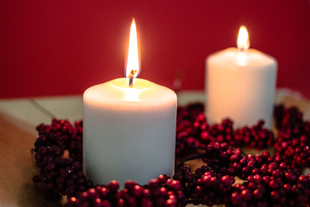 christmas perfume: Lit candles for christmas on red background