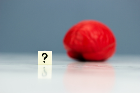 unknown age: Red brain with question mark on dark background