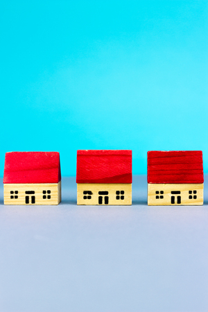 housing prices: Figurine wooden houses on blue background