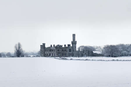 covered fields: Snow covered fields surround a derelict castle style house.