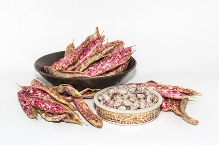 Closeup of bowl with pinto beans in pods on white background Standard-Bild