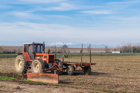 Agricultural Landscape with farm implements, tractor wagon and shovel leveling