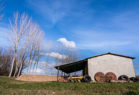 agricultural tools: old shelter for agricultural tools, with trees in the background