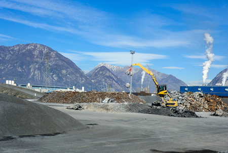 wastes: Treatment plant wastes of foundry, with excavator and crane, with mountains in the background Stock Photo