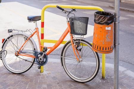 receptacle: Trash metal orange waste of road, and bicycle
