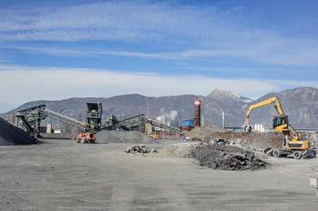 foundry: Treatment plant wastes of foundry, with excavator and crane, with mountains in the background Stock Photo