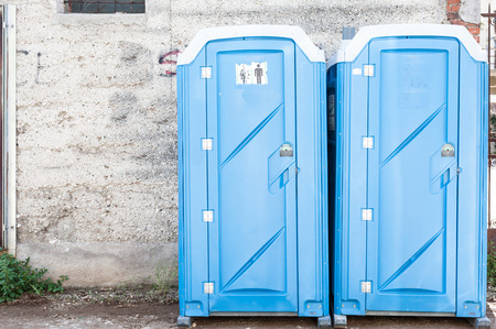 Two blue portable toilet cabins at construction site 版權商用圖片
