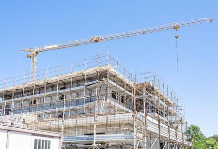 Gebäude im Bau mit Kran und Baugerüst