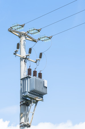 isolator insulator: Electrical transformer of electrical pylon against the blue sky