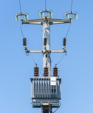 Electrical transformer of electrical pylon against the blue sky