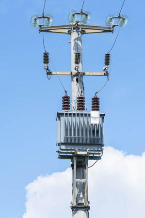 isolator: Electrical transformer of electrical pylon against the blue sky